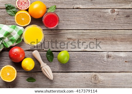 Fresh ripe citruses and juice. Lemons, limes and oranges on wooden background. Orange and red orange juices. Top view with copy space - stock photo
