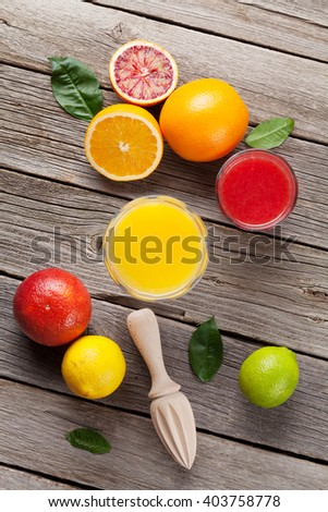 Fresh ripe citruses and juice. Lemons, limes and oranges on wooden background. Top view - stock photo