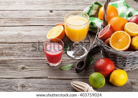 Fresh ripe citruses and juice. Lemons, limes and oranges on wooden background. View with copy space - stock photo
