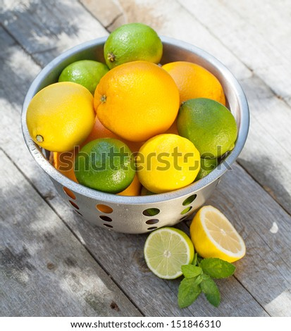 Fresh ripe citruses in colander on wood table - stock photo