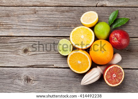 Fresh ripe citruses. Lemons, limes and oranges on wooden table. Top view with copy space. Juicer for citrus juice - stock photo