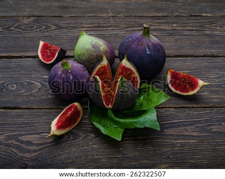 Fresh ripe Figs in blue plate on vintage wooden background
