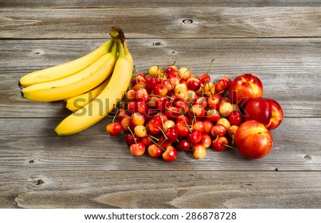 Fresh ripe fruit consisting of cherries, peaches and bananas on rustic wood.  - stock photo