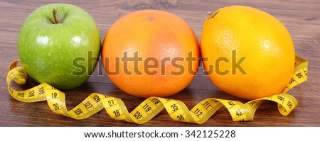 Fresh ripe fruits and tape measure on wooden surface plank, grapefruit orange apple, healthy lifestyles nutrition and strengthening immunity - stock photo