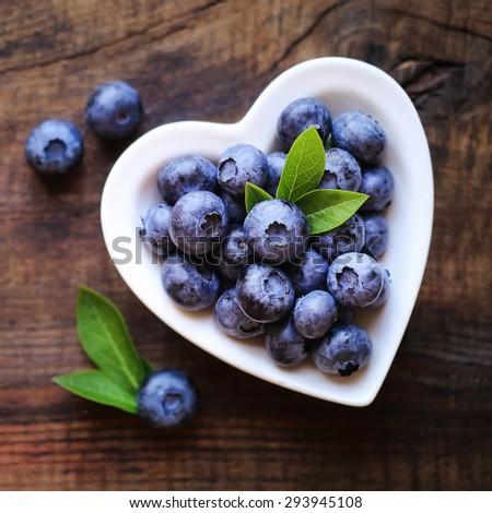 Fresh ripe garden blueberries in a white heart shape bowl on dark rustic wooden table.  - stock photo