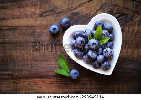 Fresh ripe garden blueberries in a white heart shape bowl on dark rustic wooden table. with copy space for your text - stock photo