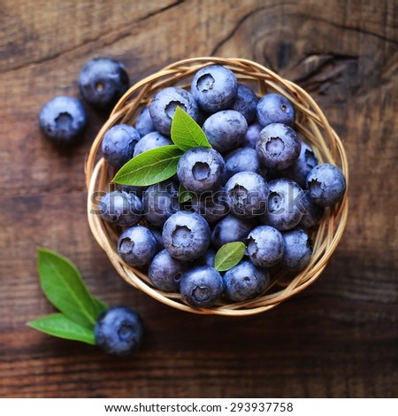 Fresh ripe garden blueberries in a wicker bowl on dark rustic wooden table.  - stock photo