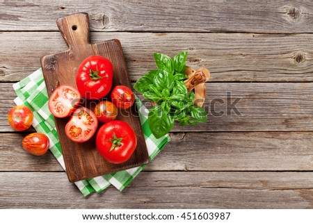 Fresh ripe garden tomatoes and basil on wooden table. Top view with copy space