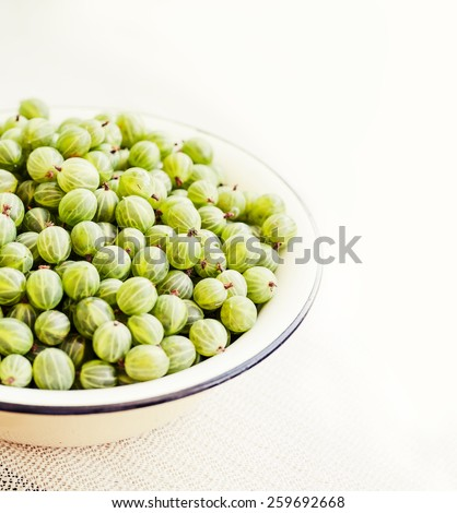 Fresh ripe gooseberries on a white wooden board. - stock photo
