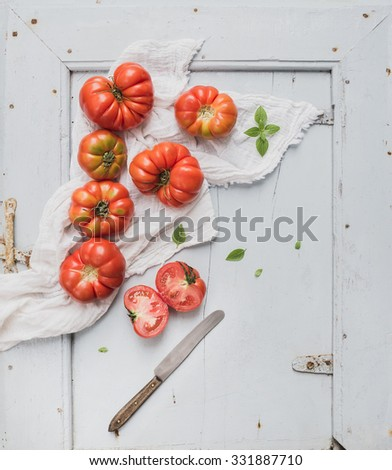 Fresh ripe hairloom tomatoes and basil on rustic blue wooden surface, top view, copy space - stock photo