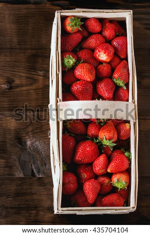 Fresh ripe juice strawberries in wood square basket over dark wooden background. Top view - stock photo