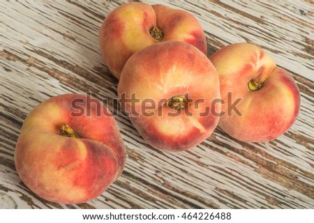 Fresh Ripe Juicy Flat Peaches Fruit on a Wooden Background