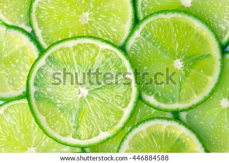 Fresh ripe juicy lime circle shaped slices close-up as background. Top view point. - stock photo