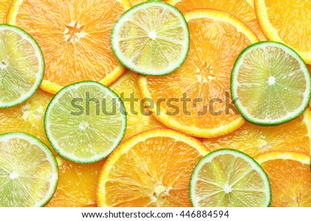Fresh ripe juicy orange and lime circle shaped slices close-up as background. Top view point. - stock photo