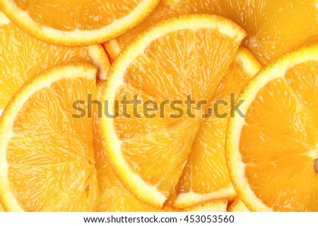 Fresh ripe juicy orange segment shaped slices close-up as background. Top view point. - stock photo