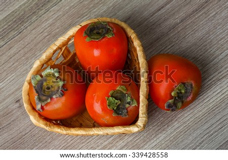 Fresh ripe juicy Persimmon fruit on the wood background - stock photo