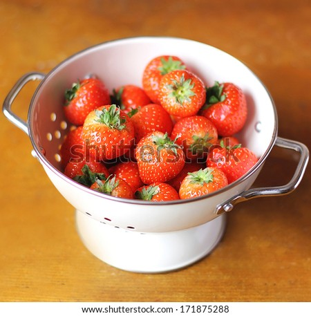 Fresh ripe juicy strawberry harvest or crop in a white colander - stock photo