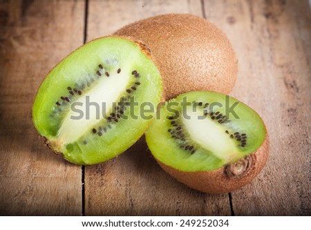 Fresh ripe kiwi on the wooden background - stock photo