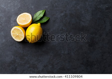 Fresh ripe lemons on dark stone background. Top view with copy space - stock photo