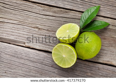 Fresh ripe limes on wooden table. Top view with copy space - stock photo