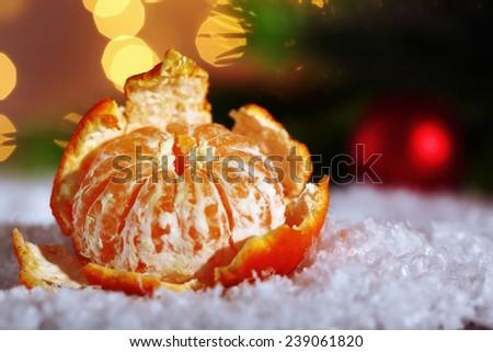 Fresh ripe mandarin on snow, on lights background - stock photo