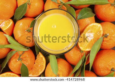 Fresh ripe mandarines with green leaves and orange juice seamless backdrop, flat lay, top view. Organic fresh mandarines, healthy fruit eating.  - stock photo