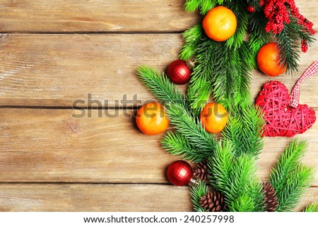 Fresh ripe mandarins, Christmas decorations and fir tree bud on wooden background - stock photo
