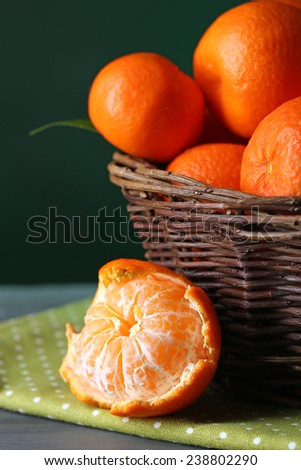 Fresh ripe mandarins in wicker basket, on wooden  table, on color background - stock photo