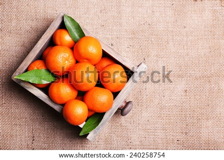Fresh ripe mandarins in wooden box, on sackcloth background  - stock photo