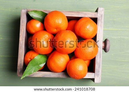 Fresh ripe mandarins in wooden box, on wooden background  - stock photo