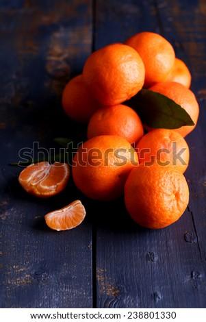 Fresh ripe mandarins on dark wooden background - stock photo