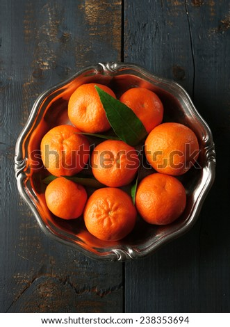 Fresh ripe mandarins on plate, on wooden background - stock photo
