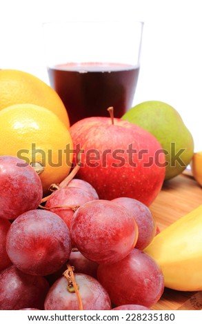 Fresh ripe natural fruits and glass of juice on wooden cutting board, apple grapes lemon, orange, pear, banana, concept for healthy eating
