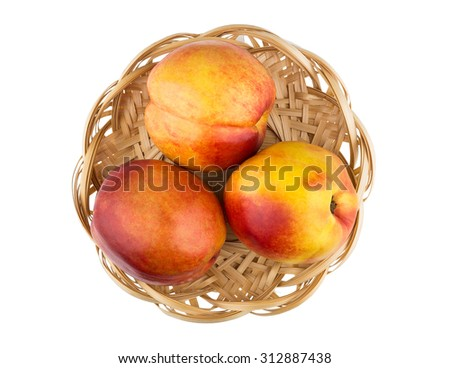 Fresh ripe nectarines in wicker basket isolated on white background, top view - stock photo