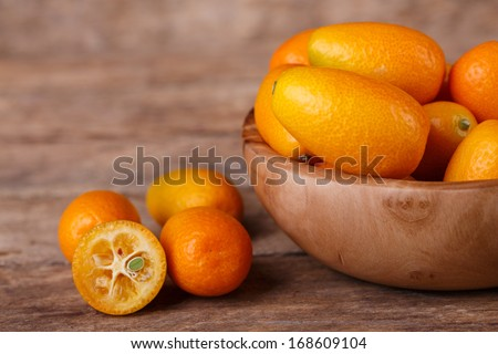 Fresh, ripe, orange kumquats  on wooden background - stock photo