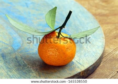 fresh ripe orange mandarins (tangerines) on a wooden table - stock photo