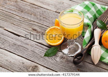 Fresh ripe oranges and juice on wooden table. View with copy space - stock photo
