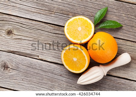 Fresh ripe oranges and juicer on wooden table. Top view with copy space - stock photo