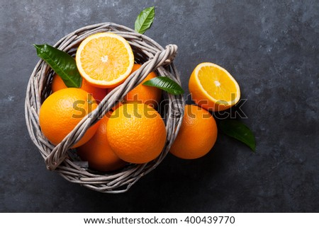 Fresh ripe oranges in basket on dark stone background. Top view - stock photo