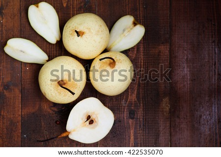 Fresh ripe organic pears on a rustic wooden table, top view - stock photo