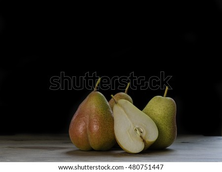 fresh ripe organic pears on wooden table with black background