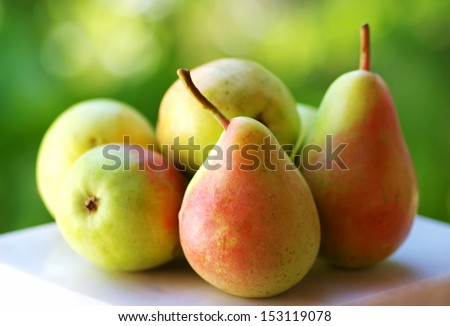 Fresh ripe pears on green background - stock photo