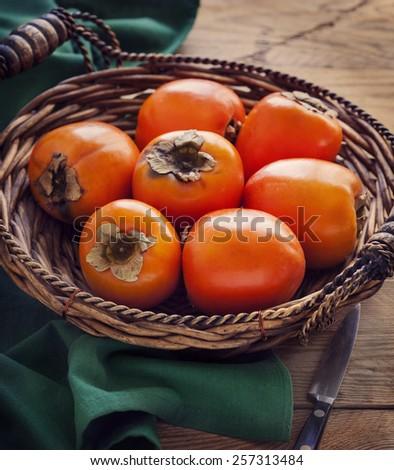 Fresh ripe persimmons. Toned image - stock photo