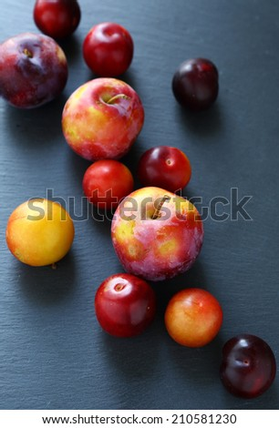 Fresh ripe plum on a gray background, food closeup - stock photo