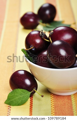 Fresh ripe plums in white bowl. Selective focus, shallow dof - stock photo