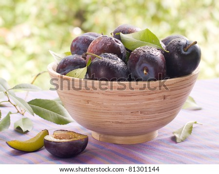 Fresh ripe plums in wooden bowl. Selective focus - stock photo
