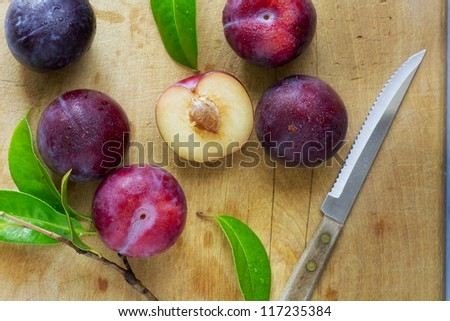 Fresh ripe plums on a chopping board - stock photo