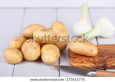 Fresh, ripe potatoes on  a  wooden background - stock photo