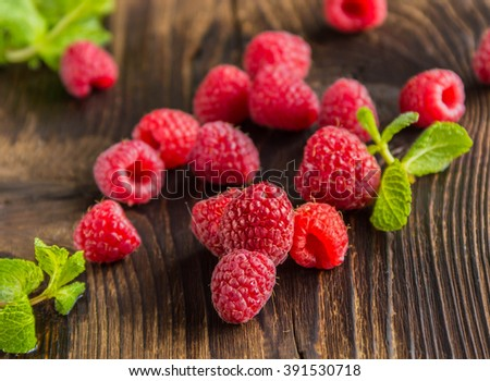 Fresh ripe raspberries and mint's leafs on old wooden table - stock photo