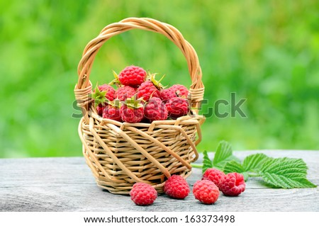Fresh ripe raspberries in the wicker basket on wooden table - stock photo